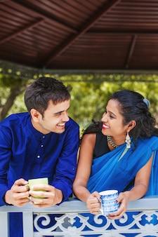バルコニーでお茶を飲み、話している美しいインドのカップル