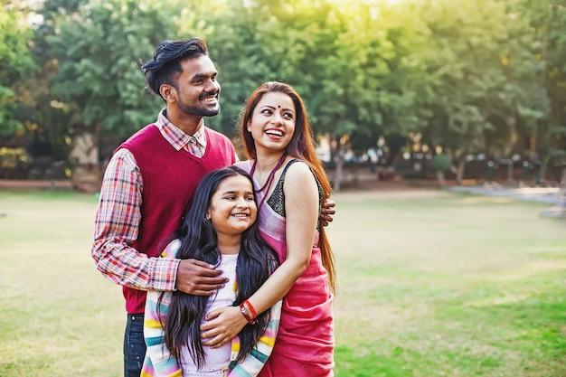 공원에 함께 서 있는 10세 딸과 함께 한 아름다운 인도 가족