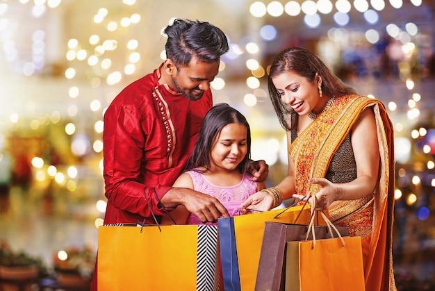 Красивая индийская семья с маленькой дочкой за покупками