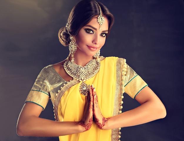 伝統的な国民のスーツの一時的な刺青ヘナの入れ墨に身を包んだ美しいインドの女の子は彼女の手に描かれ、伝統的なクンダンスタイルのジュエリーセットはナマステに挨拶のジェスチャーを示しています