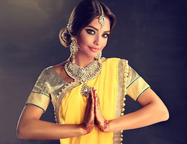 Beautiful indian girl dressed in a traditional national suit mehndi henna tattoo is painted on her hands and traditional kundan style jewelry set is showing a gesture of greeting  namaste