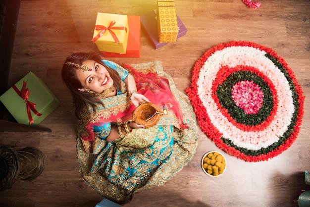 Красивая индийская девушка держит дия в ночь фестиваля дивали, вид сверху. выборочный фокус