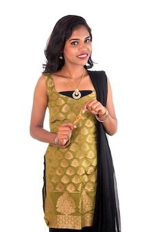 ラクシャバンダンの機会にラクヒスを示す美しいインドの女の子。