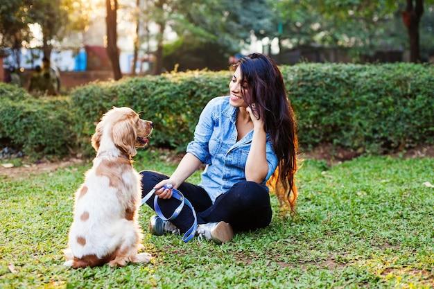 Красивая индийская девушка тренирует свою собаку кокер-спаниель