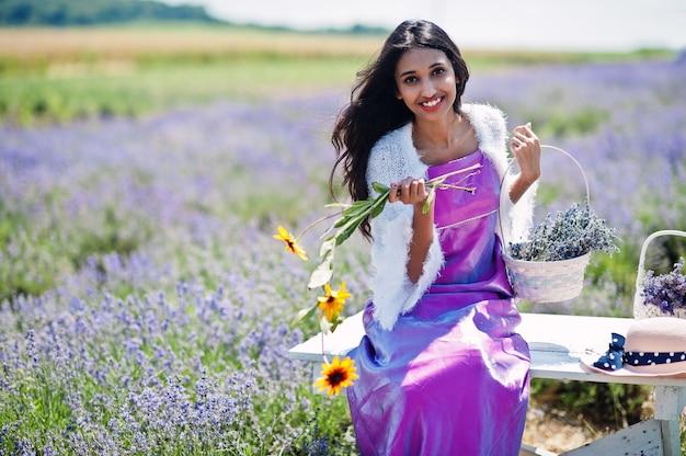 美しいインドの女の子は紫色のラベンダー畑でサリーインドの伝統的なドレスを着ています。