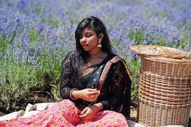 Beautiful indian girl wear saree india traditional dress in purple lavender field.