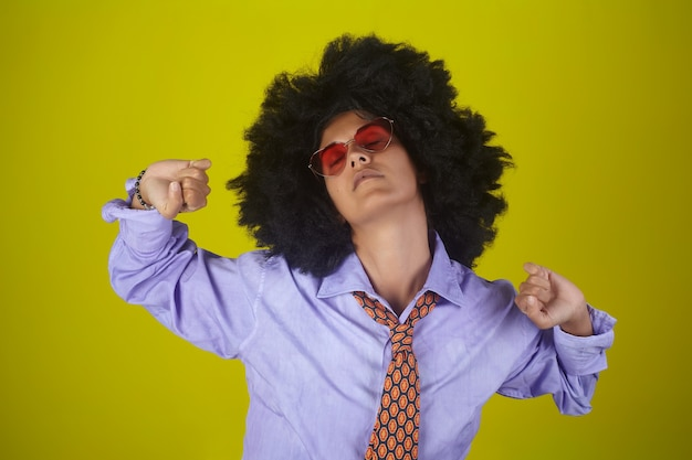 目を覚ます、黄色の壁でストレッチアフロの巻き毛のヘアスタイルと男性服の美しいインドの女の子