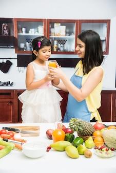 果物や野菜でいっぱいのテーブルとキッチンで美しいインドまたはアジアの若い母と娘