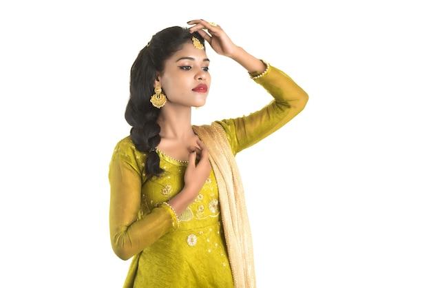 白い壁にポーズをとって美しいインドの伝統的な女の子。