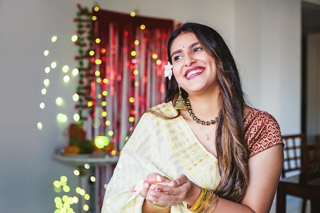 디왈리에서 디야를 들고 있는 아름다운 인도 여성