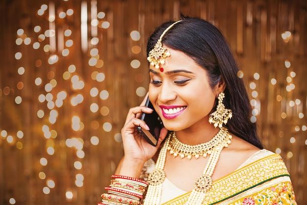 Красивая индийская женщина в традиционной одежде разговаривает по телефону