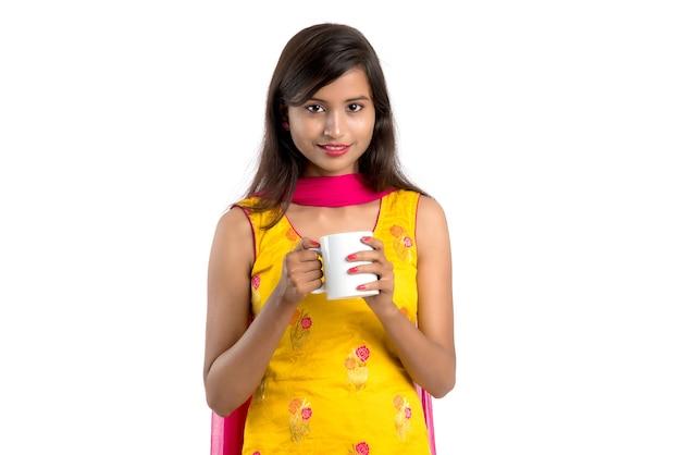 お茶を飲む伝統的なサリーを身に着けている美しいインドの女性