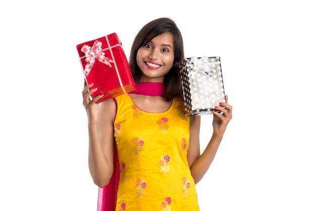 贈り物を保持している伝統的なサリーを身に着けている美しいインドの女性