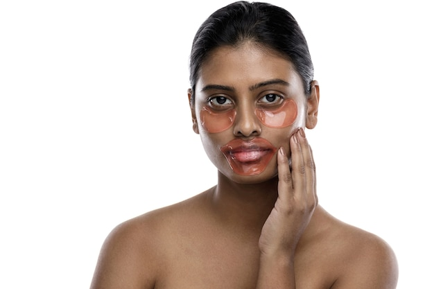 Beautiful indian woman with hydrating eye patches and lip mask on her face. isolated on white.