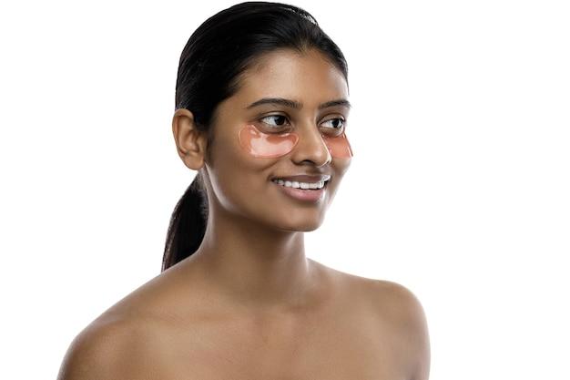 彼女の目の下に水分補給眼帯を持つ美しいインドの女性。白で隔離。