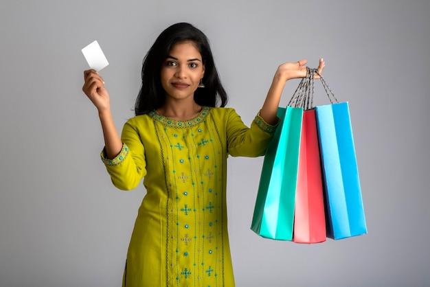 회색에 쇼핑백과 신용 카드를 들고 포즈를 취하는 아름다운 인도 소녀