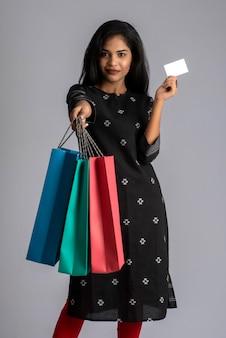 灰色の買い物袋とクレジットカードを持ってポーズをとって美しいインドの少女