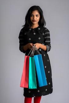 Красивая индийская молодая девушка держит и позирует с хозяйственными сумками на сером фоне