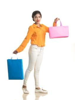 Красивая индийская молодая девушка держит и позирует с хозяйственными сумками на белой стене