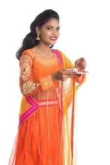 プージャタリを持っているか、礼拝をしている美しいインドの少女