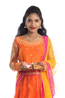 Beautiful indian young girl holding pooja thali or performing worship on a white wall