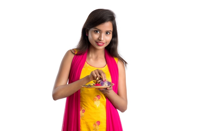 Beautiful indian young girl holding pooja thali or performing worship on a white