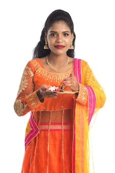 Beautiful indian young girl holding pooja thali or performing worship on white