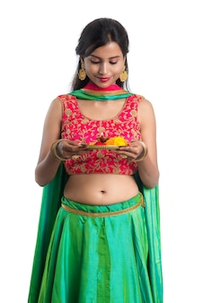 Beautiful indian young girl holding pooja thali or performing worship