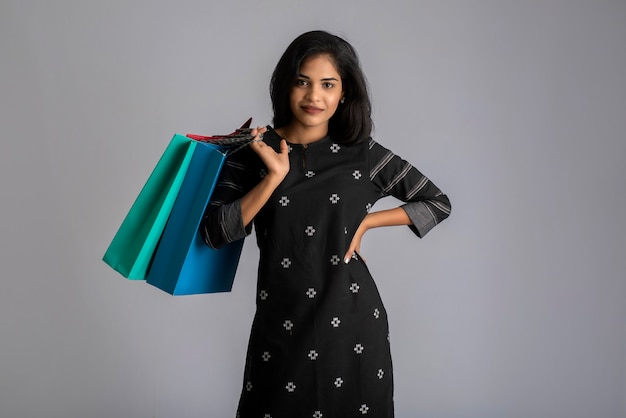 Beautiful indian young girl holding and posing with shopping bags on a grey background