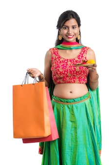Beautiful indian young girl holding and posing with shopping bags and pooja thali on a white space