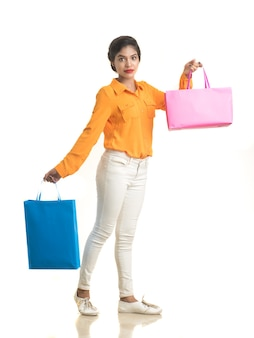 Beautiful indian young girl holding and posing with shopping bags on a white wall