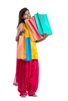 Beautiful indian young girl holding and posing with shopping bags on a white