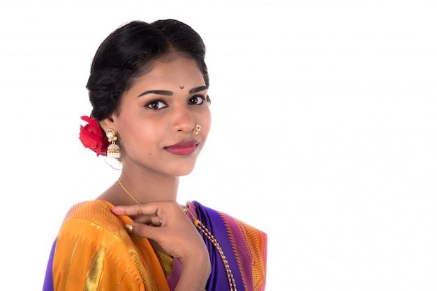 Красивая индийская маленькая девочка представляя в традиционном индийском сари на белом космосе.