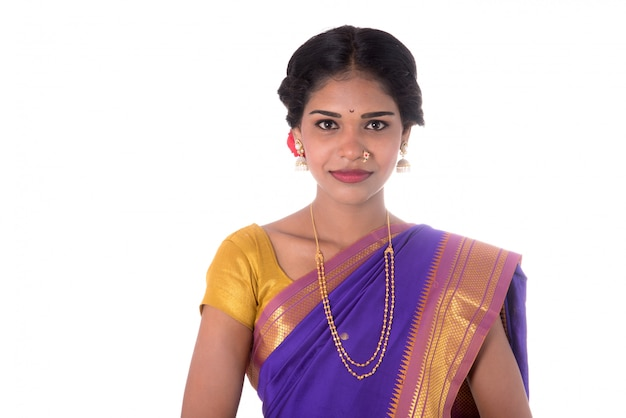 Beautiful indian young girl posing in traditional indian saree on white wall