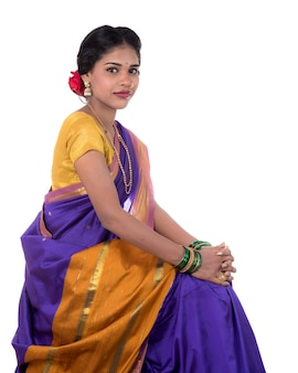 Beautiful indian young girl posing in traditional indian saree on white wall.