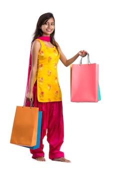 Красивая индийская молодая женщина, держащая и позирующая с хозяйственными сумками