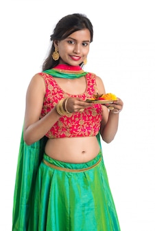 Beautiful indian young woman holding pooja thali or performing worship on white