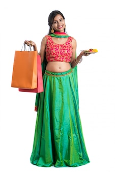 Beautiful indian young woman holding and posing with shopping bags and pooja thali on a white wall