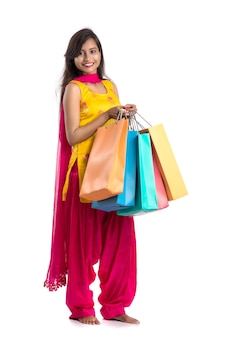 Beautiful indian young woman holding and posing with shopping bags