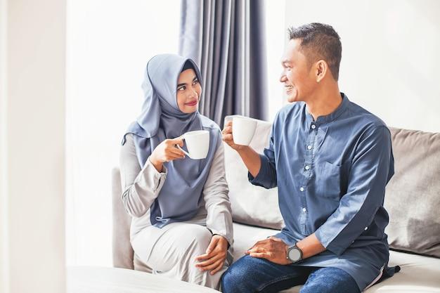 집에서 커피를 마시는 아름다운 인도네시아 이슬람 부부