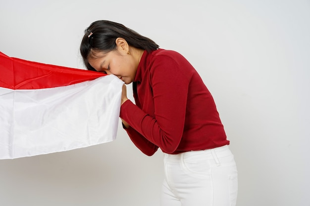 Beautiful indonesian woman kissing the flag of indonesia