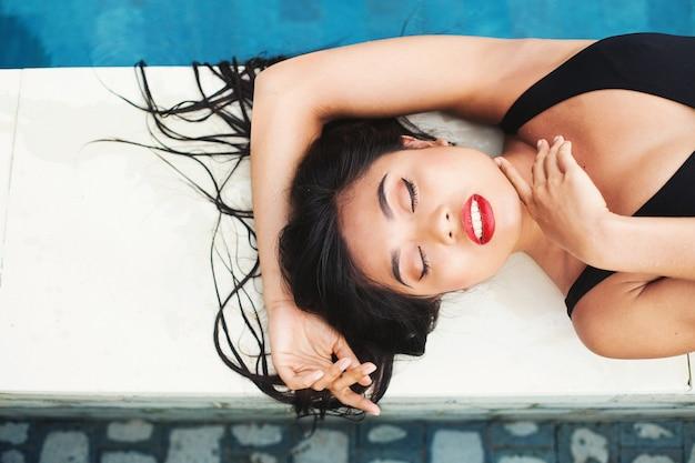 Красивая индонезийская женщина, лежа у бассейна