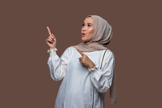 驚きに満ちた表情で手を指してポーズをとる美しいインドネシアの女性