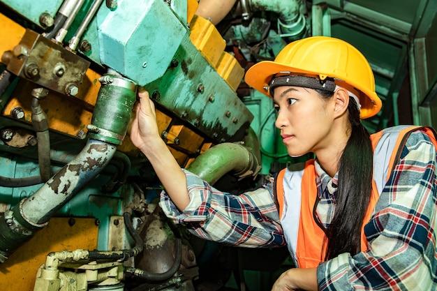 ヘルメットをかぶった鉄道駅のガレージ プラントの美しい産業労働者チェックとエンジンについて