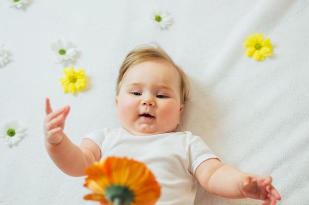 Красивый младенческий младенец лежа на белых листах достигая для цветка.