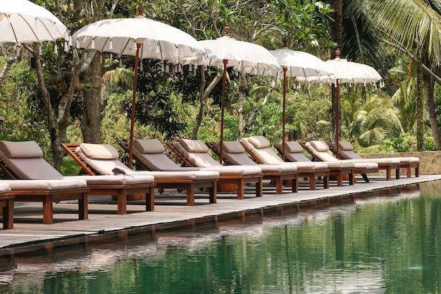 トロピカルガーデンの美しいインフィニティプール、サンベッドと傘を持つ観光客のためのリラクゼーションエリア、バリ島、インドネシア