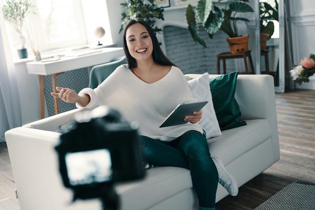 美しいインフルエンサー。彼女のブログの新しいビデオを作成しながら身振りで示すと笑顔の魅力的な若い女性