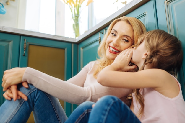 美しいインスピレーションを得た金髪の母と娘が笑顔でキッチンの床に座って、女の子が耳元でささやきます