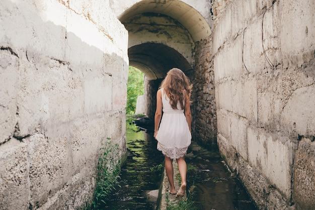 흰 드레스에 곱슬 자연 머리를 가진 아름다운 영감을받은 소녀가 터널을 걷고 있습니다.
