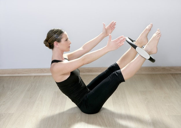 Beautiful instructor woman with magic pilates ring in sport gym
